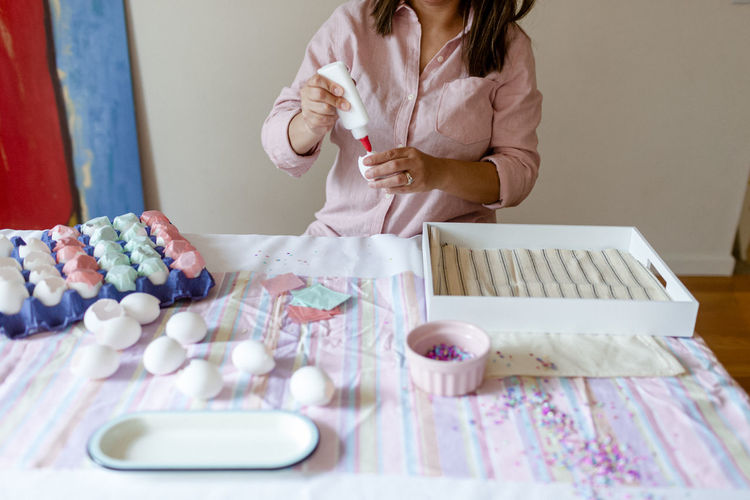Midsection of woman holding food on table at home