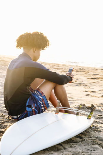 Afro surfer man consulting application on smartphone with surfboard on beach at summer sunrise
