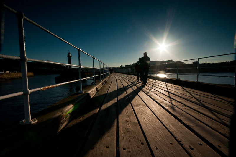 Wooden Pier Over River Against Sky During Sunny Day