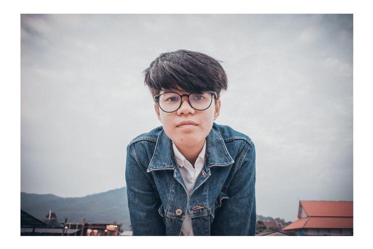 Portrait of boy standing against sky