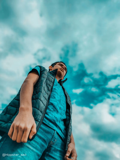 Low angle view of man relaxing against sky