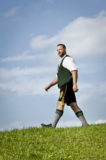 A man in bavarian traditional cloth Bavaria Bavarian Tradition Cloud - Sky Day Field Full Length Grass Green Color Growth Leather Lederhosen Leisure Activity Lifestyles Low Angle View Nature One Person Outdoors Pants Real People Sky Soccer Soccer Field Standing Tradition Typical