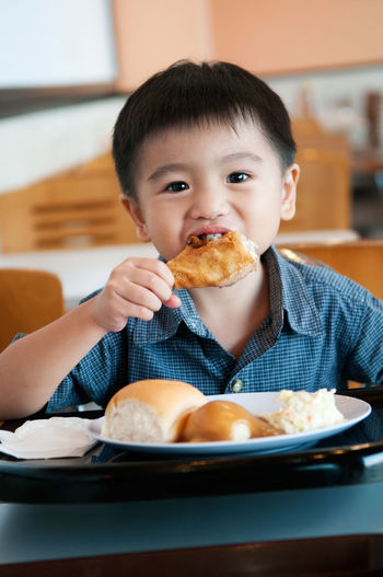 Portrait of boy eating food at home