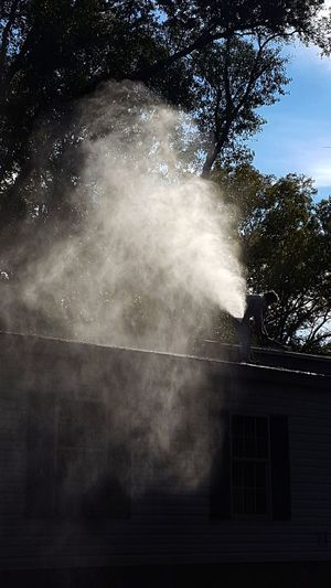 and there she blows.... Man On Rooftop Louisiana Brightly Lit Spraying Mist Tree Water Spraying Sky Streaming