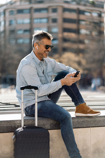 Man using mobile phone while sitting in city
