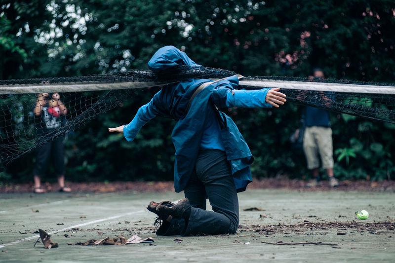 Rear view of boy in rain coats under a tennis net.