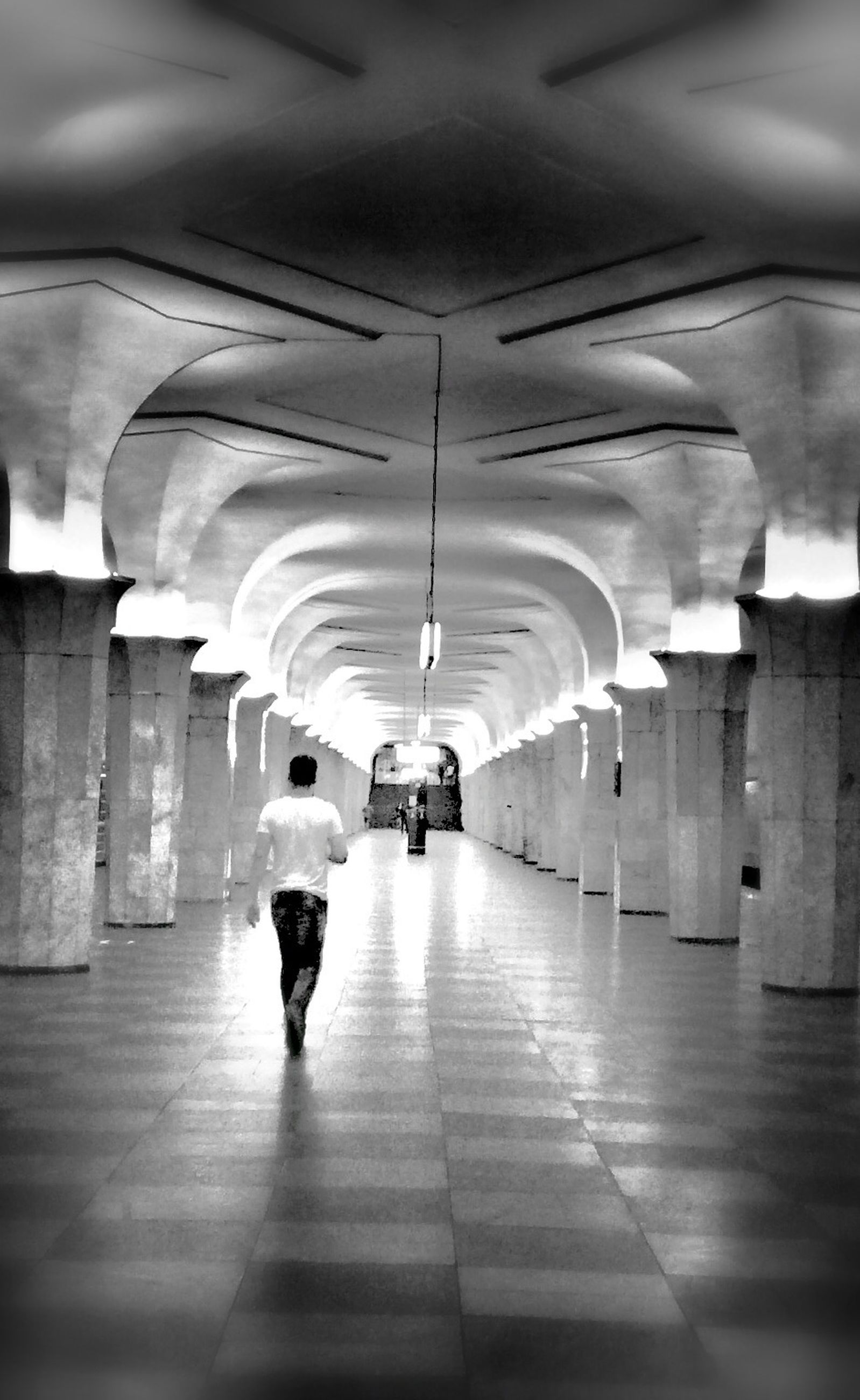 architecture, built structure, ceiling, walking, illuminated, indoors, the way forward, lighting equipment, rear view, real people, arch, architectural column, full length, one person, day, people