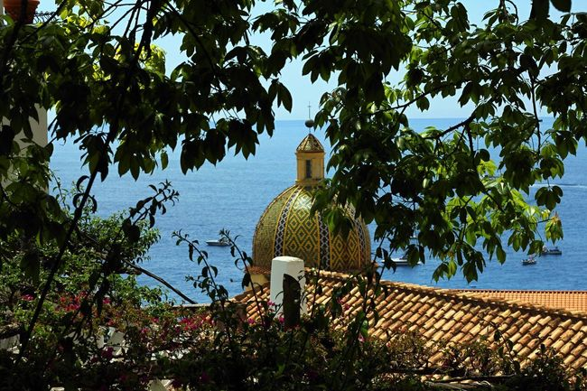 A glimpse among the leaves on the sea and the cathedral of Positano. Amalfi Coast Bright Wanderlust Architecture Bell Tower Building Exterior Built Structure Day Foreground Growth Italy Nature No People Outdoors Place Of Worship Positano Religion Sea Sky Summer Sun Travel Destinations Tree Water Waves