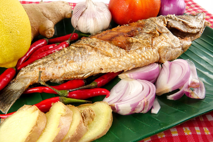 Fried Siakap fish and food decoration. Bread Chili Pepper Close-up Deep Fried  Food Food And Drink French Food Freshness Fruit Healthy Eating Indoors  Meat No People Pepper Plate Ready-to-eat Siakap Snack Spice Still Life Table Tomato Vegetable