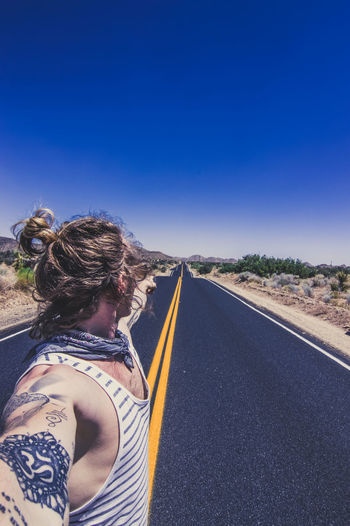 Rear view of man standing on road against clear blue sky