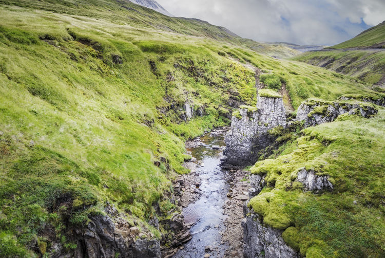 Any place in Iceland Iceland Beauty In Nature Day Environment Flowing Flowing Water Grass Green Color Land Landscape Mountain Nature No People Non-urban Scene Outdoors Plant Rock Rock - Object Scenics - Nature Sky Solid Stream - Flowing Water Tranquil Scene Tranquility Water