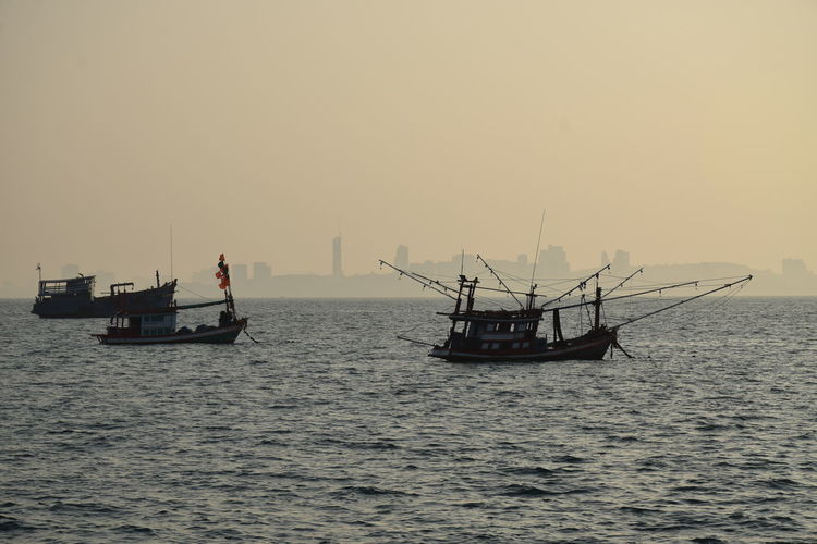 Silhouette boats sailing in sea against clear sky during sunset