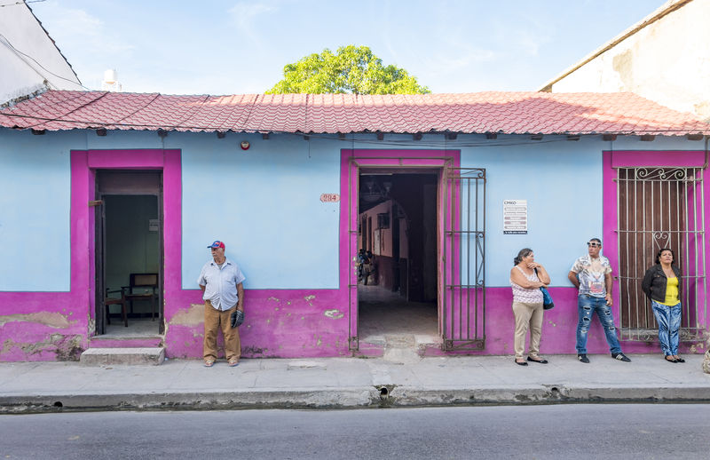 Cuban people waiting for public bus in front of a colorful colonial house Adult Adults Only Building Exterior Day Men Outdoors People Pink Color Store Women Young Adult