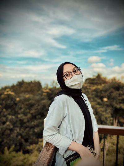 Portrait of woman wearing mask standing against sky