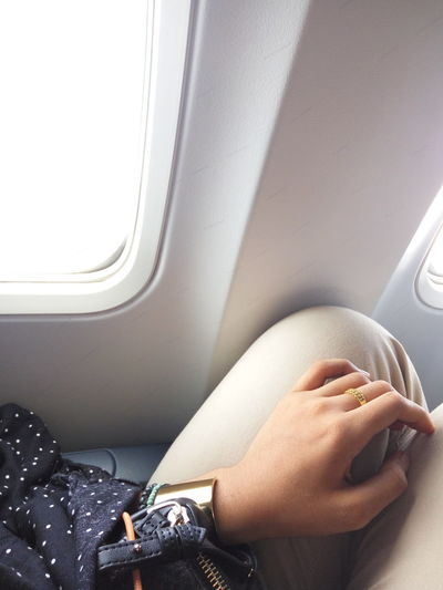 Cropped image of woman sitting by window in airplane