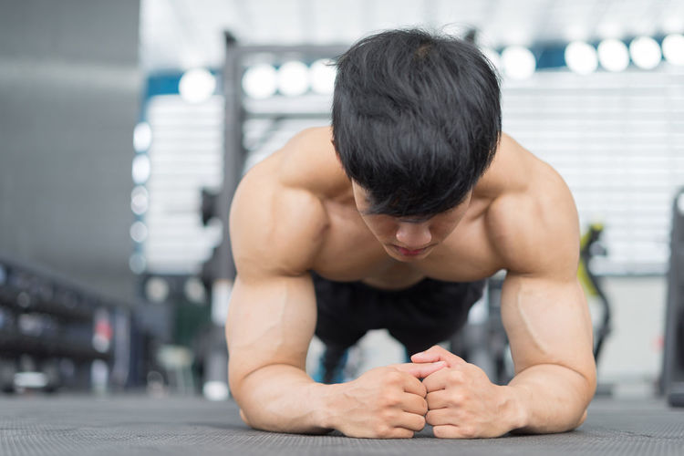 Shirtless man exercising in plank position at gym
