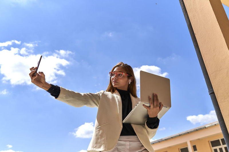 Low angle view of woman holding sunglasses against sky