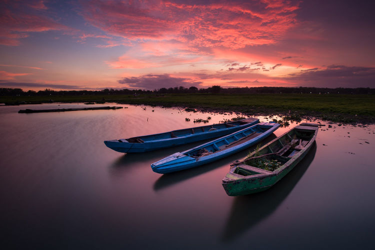 Rowboats moored in river against sky at sunset
