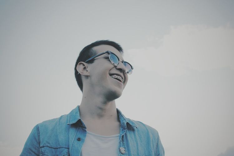 Low angle view of happy young man wearing eyeglasses against clear sky