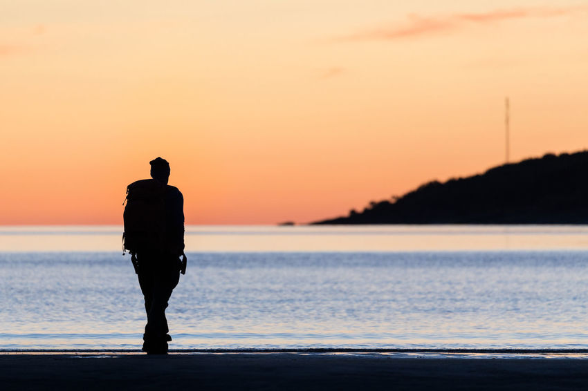 Man walking along a beach enjoying the sunset Norwegian Sea Adult Atmospheric Mood Beach Beauty In Nature Full Length Horizon Over Water Idyllic Men Mountain Nature Nordland County One Man Only One Person Orange Color Outdoors Pastel Colored Real People Rear View Relaxation Sea Silhouette Sunset Tranquil Scene Walking