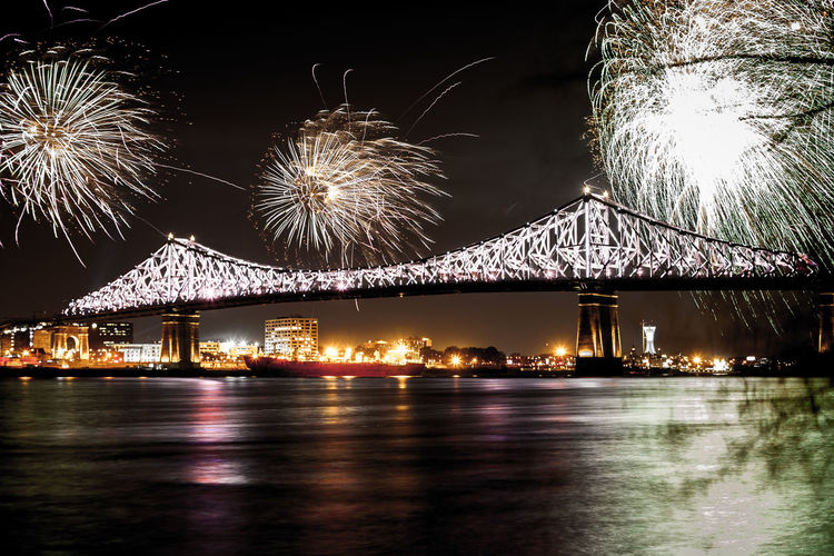 Firework display over river against sky at night