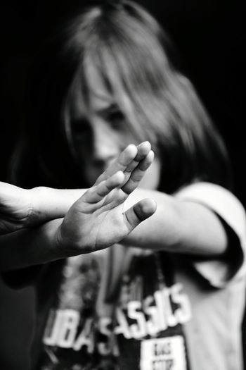 Boy with crossed hands against black background