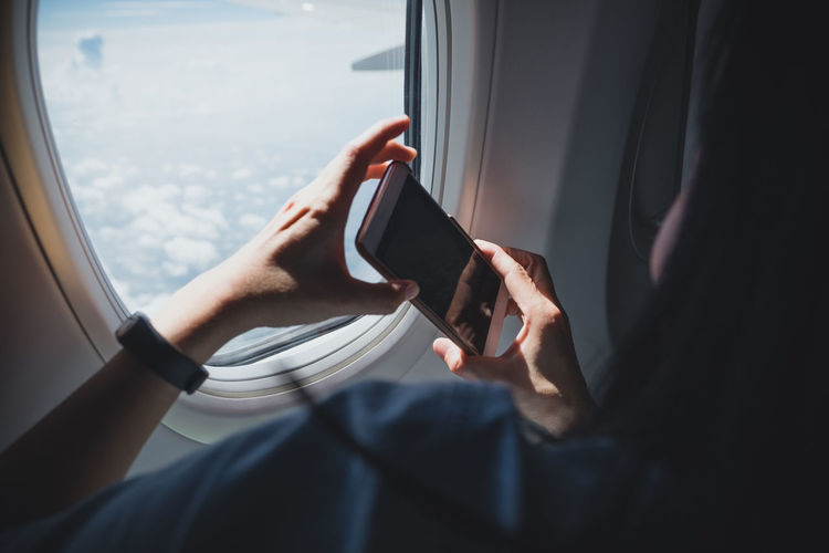 Midsection of man using mobile phone in airplane