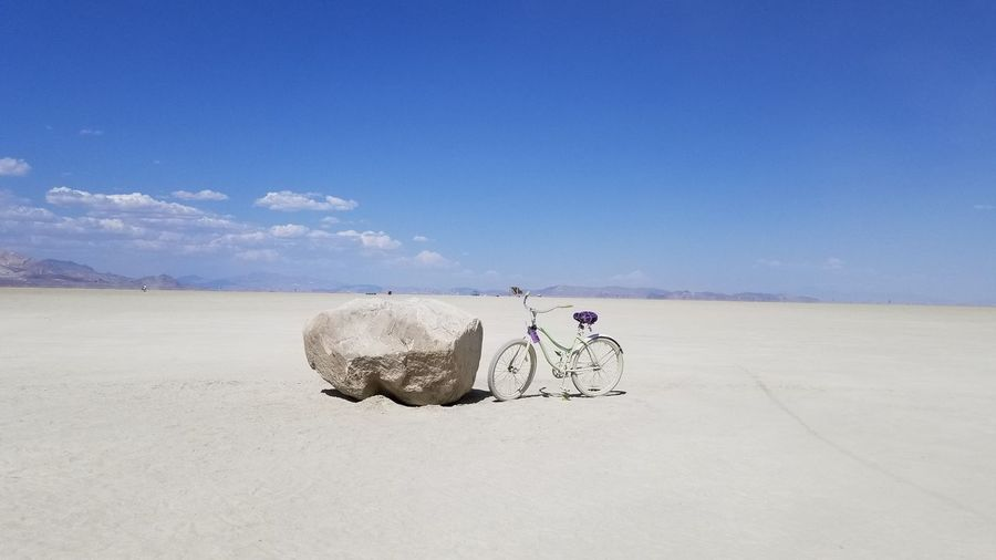 Bicycle Parked By Rock Against Sky At Desert