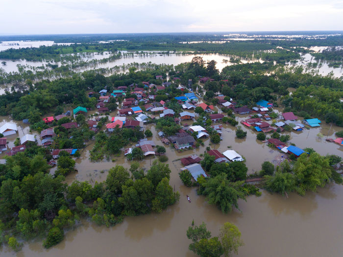 Water flood at Sakon Nakhon, Thailand Plant Water Tree Sky Architecture Scenics - Nature Built Structure Building Exterior Nature High Angle View Sea Cloud - Sky No People Day Growth Beauty In Nature Building Environment Outdoors Horizon Over Water TOWNSCAPE