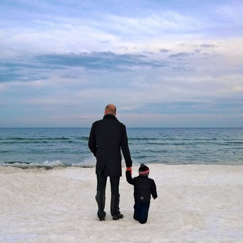 Rear View Of Father And Son Standing At Beach Against Cloudy Sky