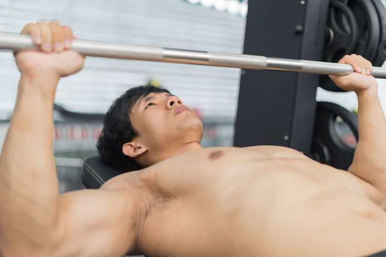 Close-Up Of Shirtless Man Exercising In Gym