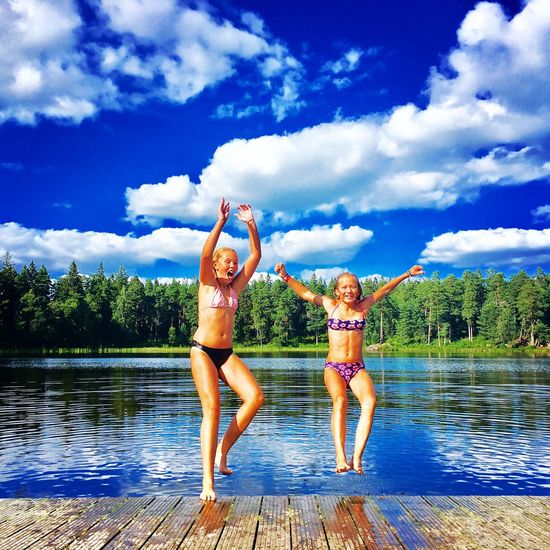 Full length of happy girls jumping in lake against sky