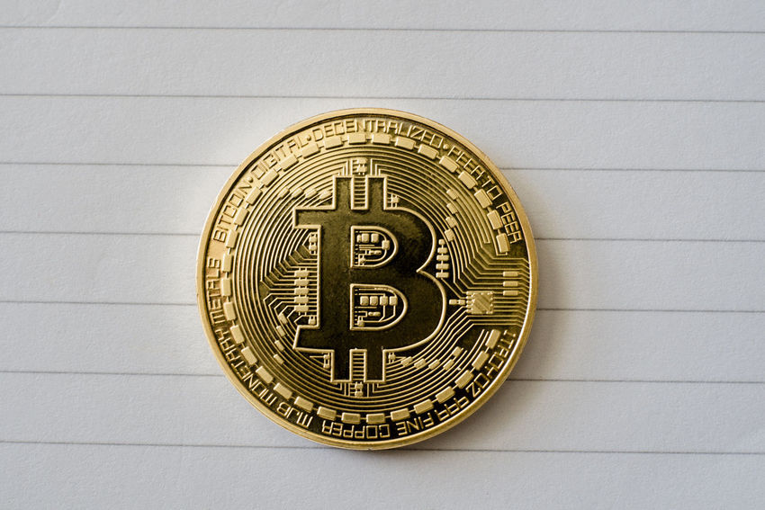 Overhead view of a single gold Bitcoin coin on notebook paper, close-up. Currency Fiat Gold Trading Algorithm Banking Bitcoin Block Chain Close-up Close—up Coin Cryptocurrency Decentralized Digital Future Investing Macro Mining Money No People Notebook Peer To Peer Single Transactions Wealth