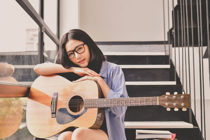 Acoustic Guitar Arts Culture And Entertainment Casual Clothing Front View Guitar Holding Indoors  Leisure Activity Lifestyles Music Musical Equipment Musical Instrument Musician One Person Playing Plucking An Instrument Portrait Real People Sitting Skill  String Instrument Teenager Young Adult Young Women