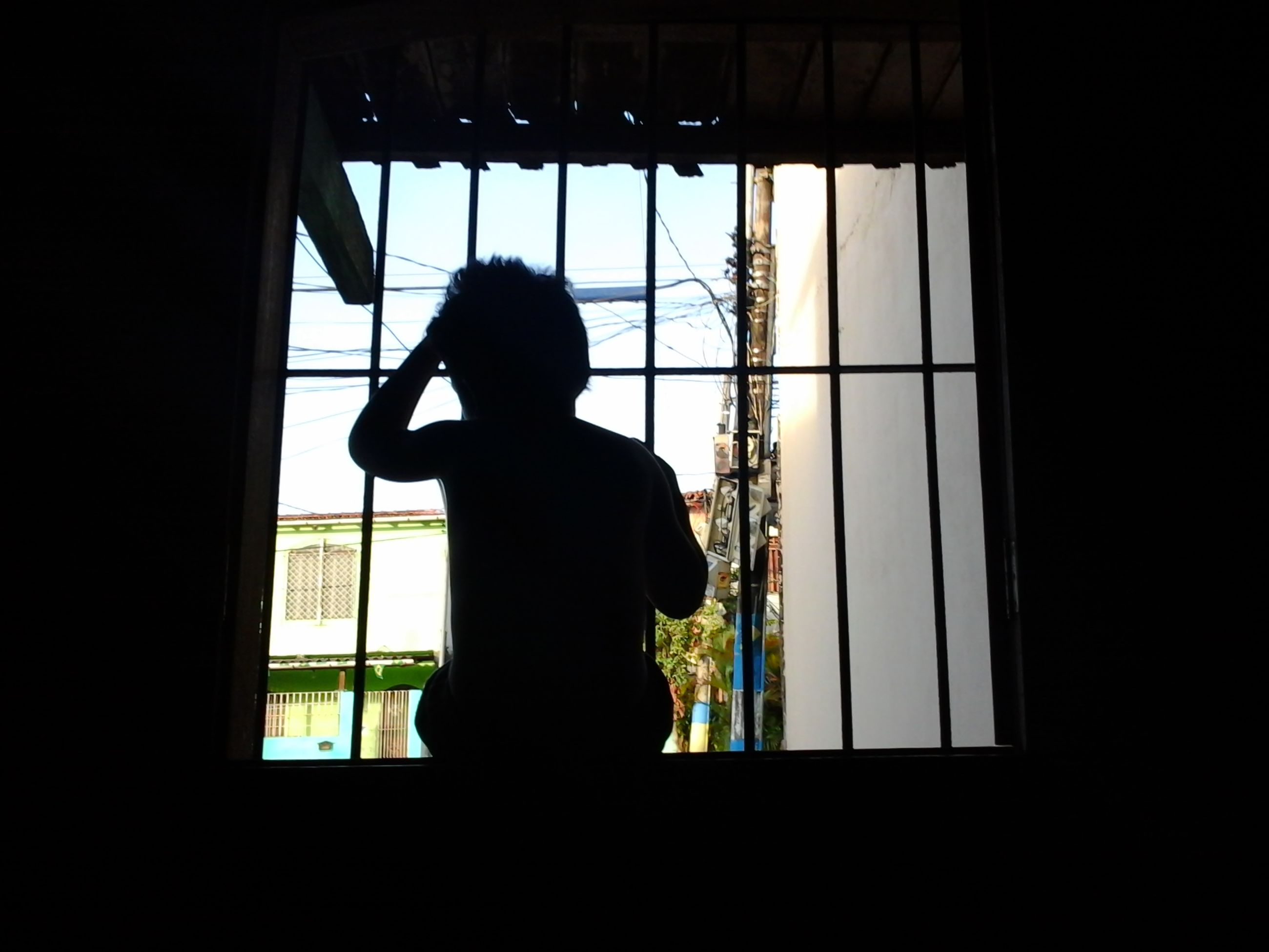 indoors, window, silhouette, standing, glass - material, transparent, lifestyles, full length, home interior, three quarter length, looking through window, rear view, leisure activity, side view, dark, low angle view, built structure, day