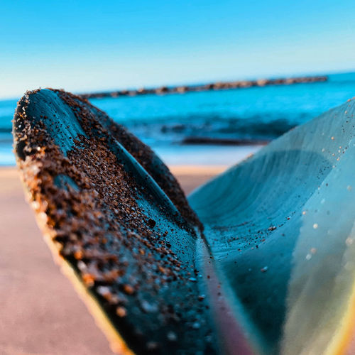 Close-up of rusty metal on beach against clear blue sky