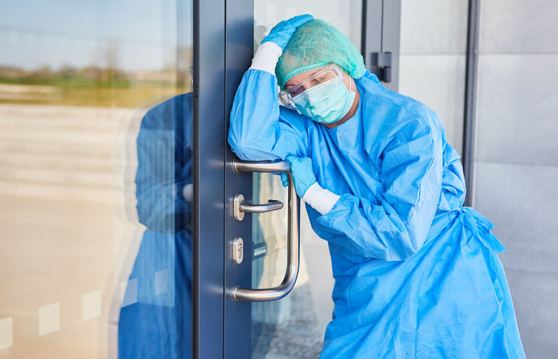 Doctor in protective clothing takes a break because of stress and exhaustion from coronavirus