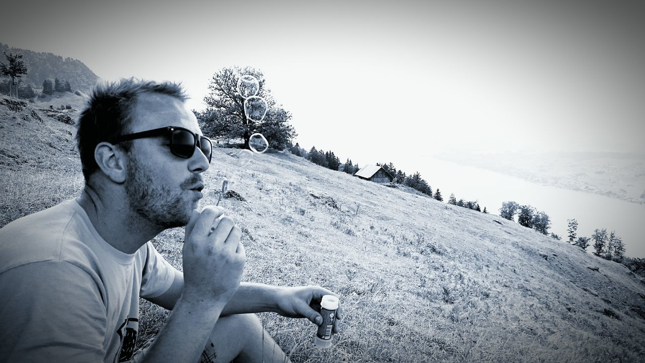 sunglasses, real people, young adult, one person, young men, outdoors, leisure activity, day, lifestyles, clear sky, bad habit, nature, looking at camera, young women, sky, sitting, portrait, tree, beauty in nature, close-up