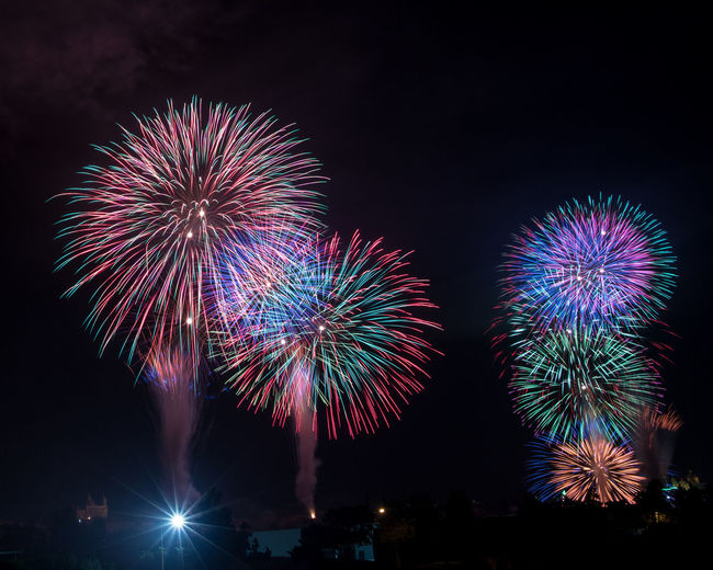 Well timed Architecture Arts Culture And Entertainment Bright Celebration City Event Exploding Firework Firework - Man Made Object Firework Display Glowing Illuminated Light Long Exposure Low Angle View Motion Multi Colored Nature New Year's Eve Night No People Outdoors Sky Sparks