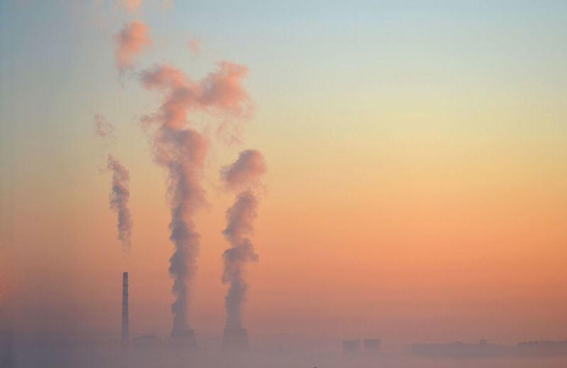 Pipe factory smoke obscured by fog background pink sky