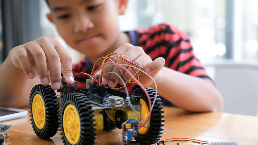 Midsection of boy repairing toy vehicle on table