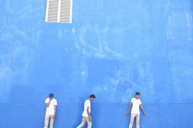 Male friends by blue wall