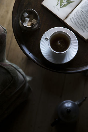 A moody mlose up with selective focus of tea cup, sugar and a book on a table. Sunset Tea Time Still Life Taking Photos Table Beverage Change Cup Negative Space Tea Cup Refreshment Close-up Sugar Cubes Saucer Selective Focus Autumn Mood