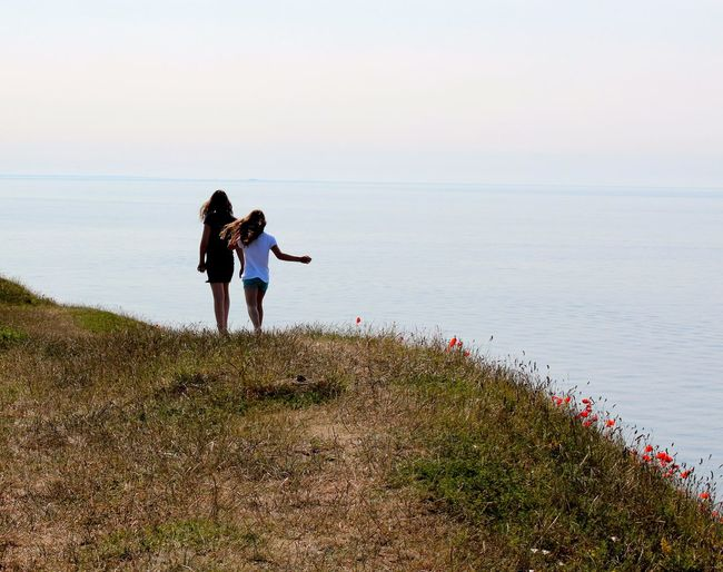 Rear view of girls walking on mountain by sea against sky