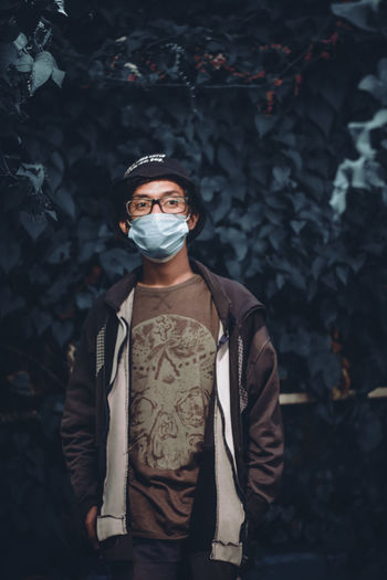 Portrait of young man standing outdoors during pandemic