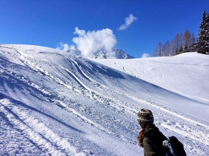 Person skiing on snow covered mountain against sky