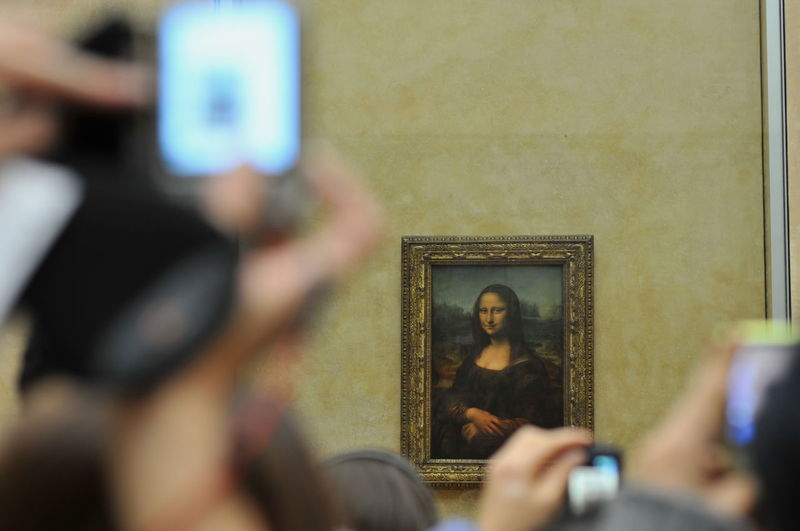 Crowd photographing mona lisa picture frame on wall