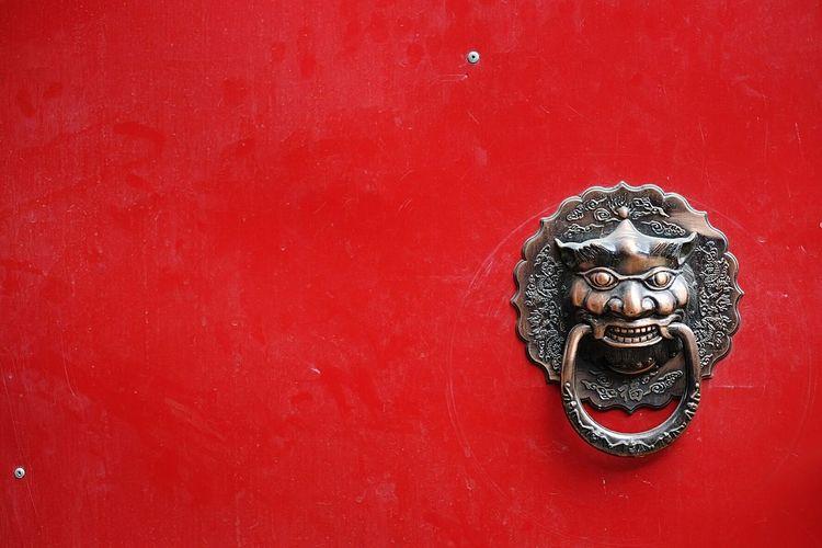 Full frame shot of red wooden door with metallic knocker