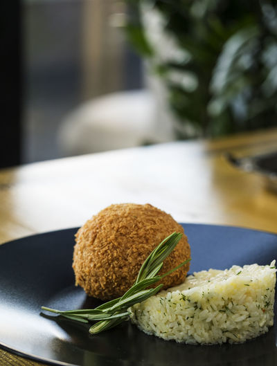 Close-Up Of Stuffed Cutlet With Rice Served In Plate