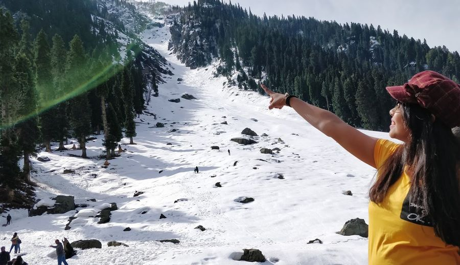 Woman pointing on snow covered land
